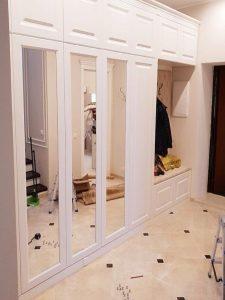 Прихожая с вешалками, зеркальным шкафом и каретным сиденьем